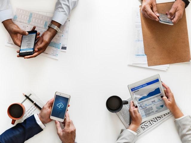čtyři lidé, ruce na jednom stole, každý drží v rukou telefon a u toho ještě něco, například kávu, noviny, nějaké podklady k jednání